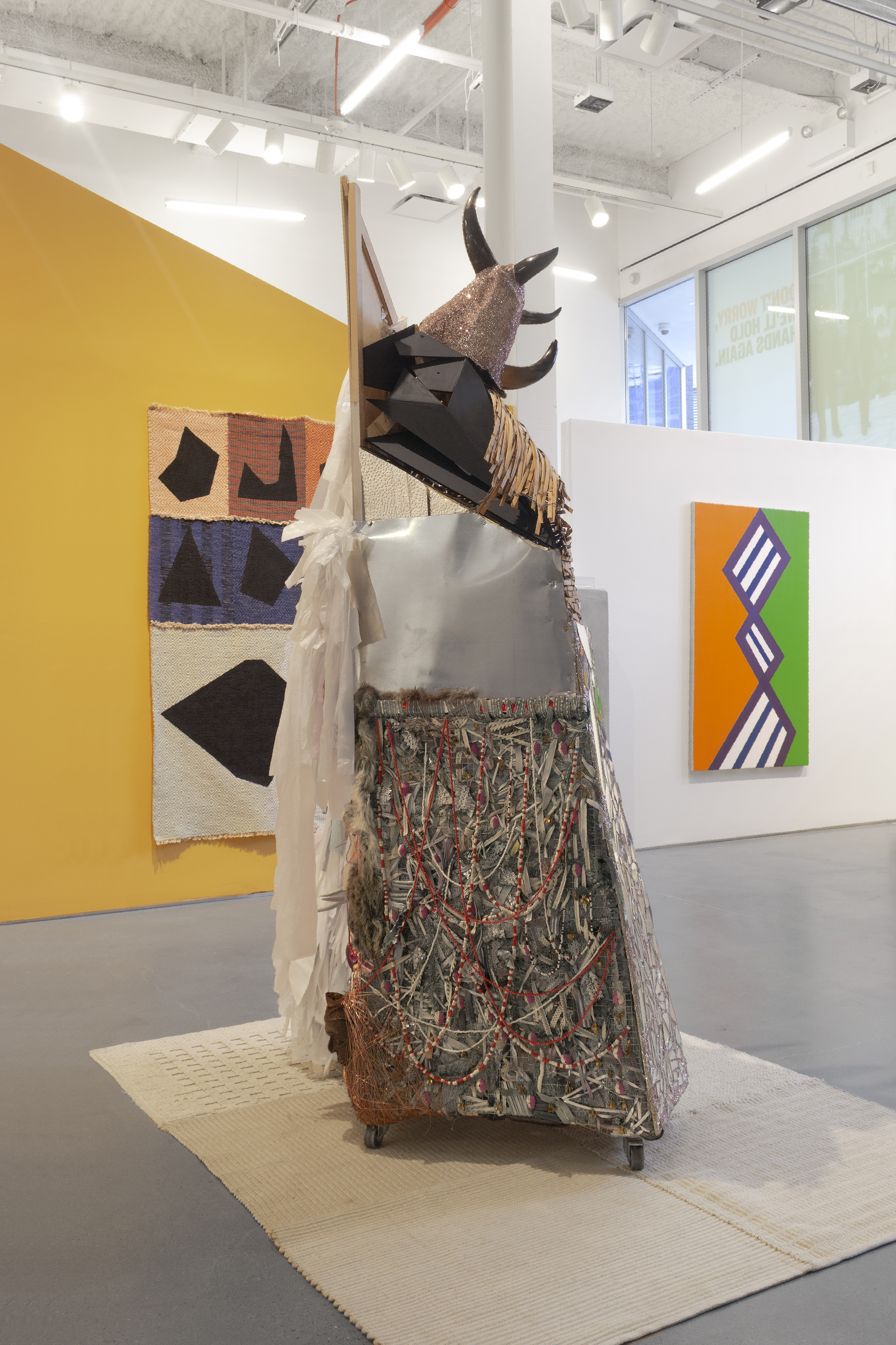 Large sculpture with a wooden frame, draped in fabric, animal fur and beads with deer antlers on top