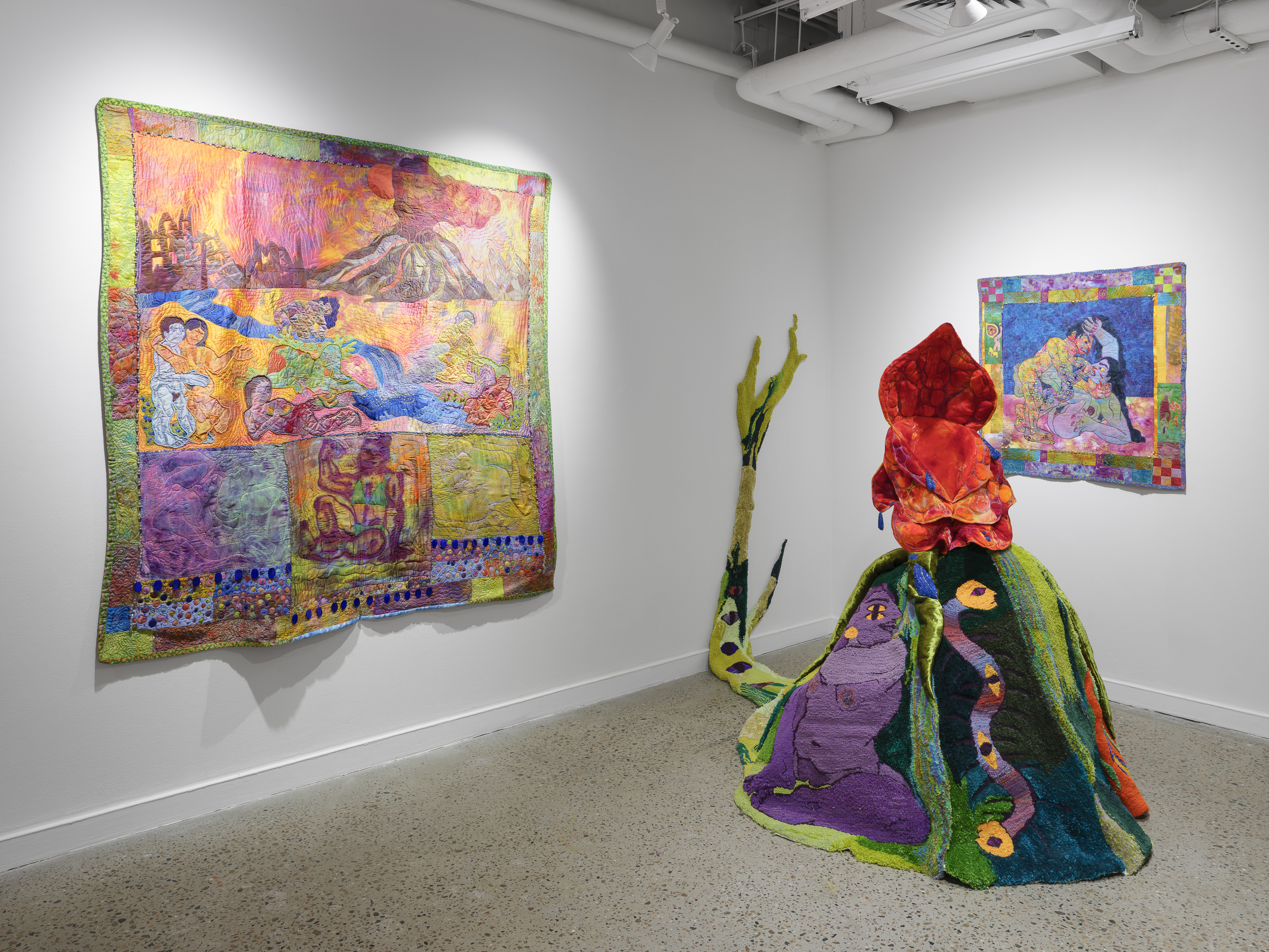 Large scale artwork on wall of gallery and on floor, depicting bright colors of abstract people, a volcano and snake..