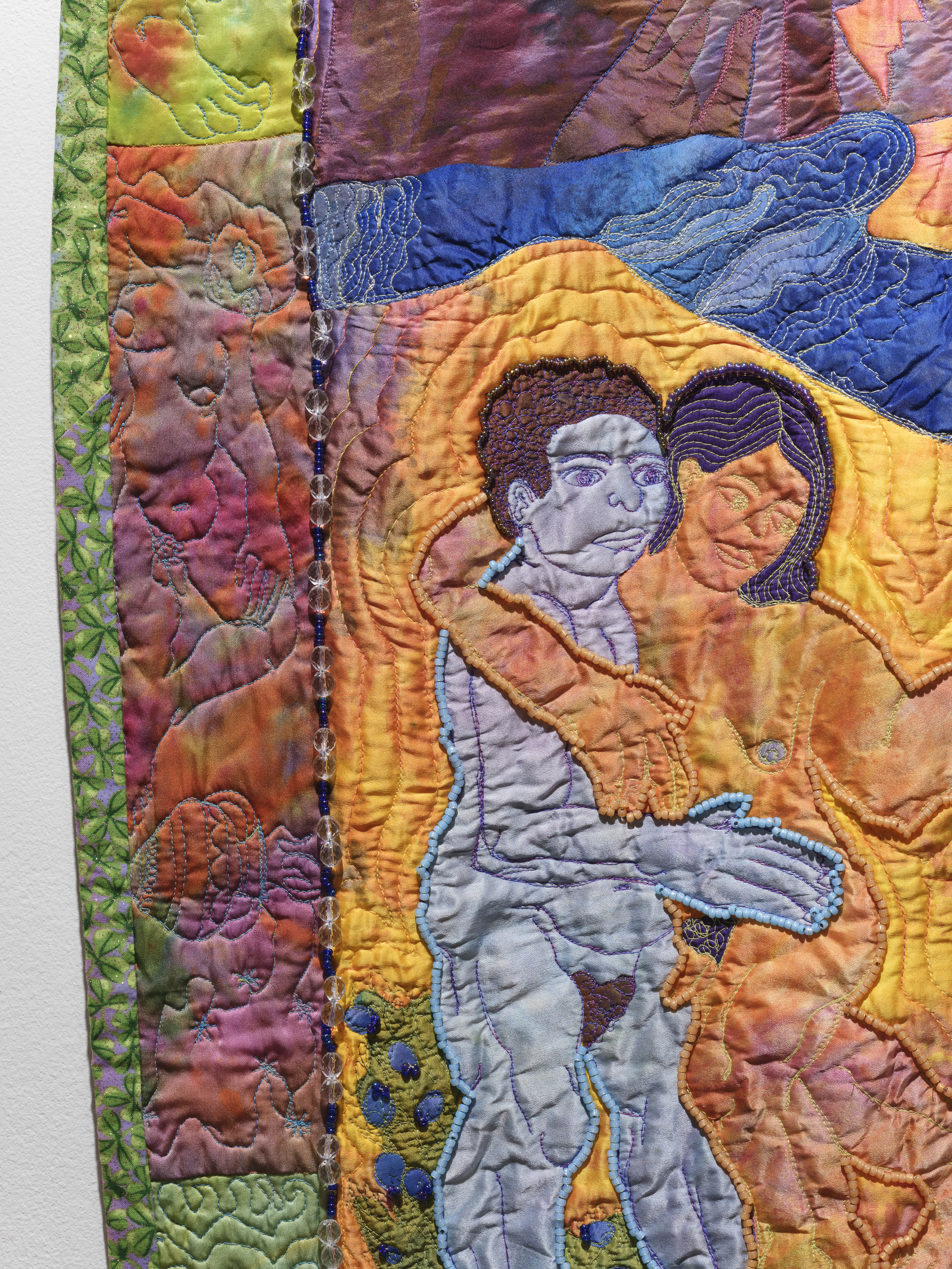 Close up of colorful, beaded artwork depicting a couple holding each other.