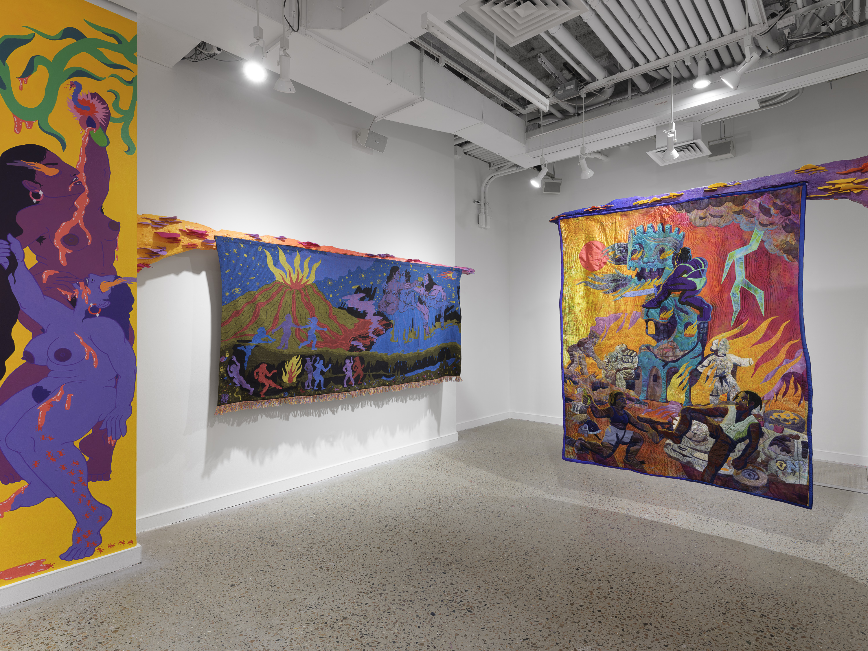 An art gallery room with three colorful and bright pieces of art hanging on the wall.